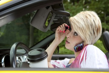 a woman doing her makeup & talking on the phone while driving