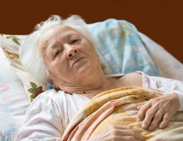 an elderly woman in a nursing home bed