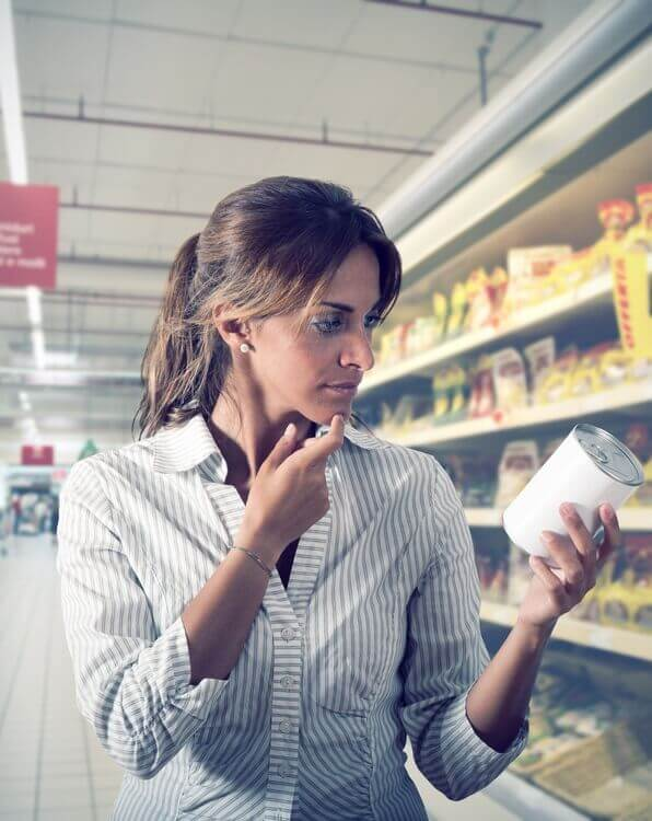 woman reading label is unsure of product at supermarket